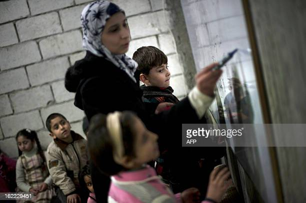 Syrian children are seen attending a makeshift school in the cellar of a building in the eastern town of Deir Ezzor on February 19 2013 A dozen steps...