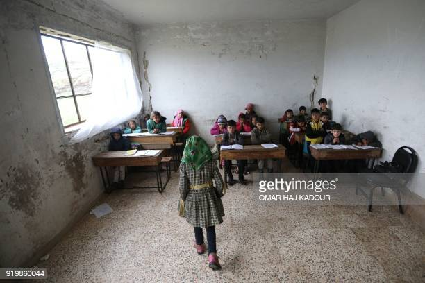 TOPSHOT Syrian children attend a class at a school in the Sahl alGhab area in Hama province on February 18 2018 / AFP PHOTO / OMAR HAJ KADOUR