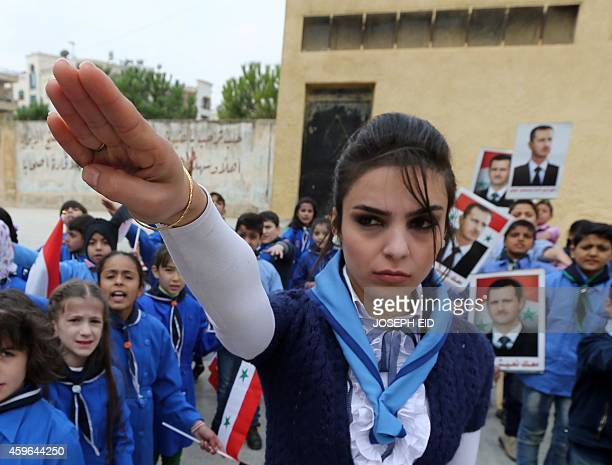 Syrian children celebrate the Correctional Movement Anniversary and the recruitment of new Baath Juniors at a school in Aleppo on November 17 2014...