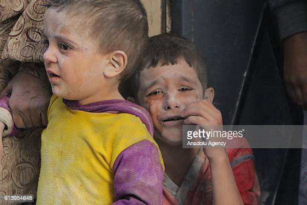 Syrian children cry after the warcrafts belonging to the Russian army bombed the opposition controlled Firdevs neighborhood in Aleppo Syria on...
