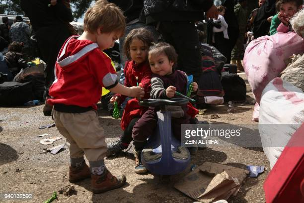 Syrian children evacuated from Eastern Ghouta play after arriving in Qalaat alMadiq some 45 kilometres northwest of the central city of Hama on March...