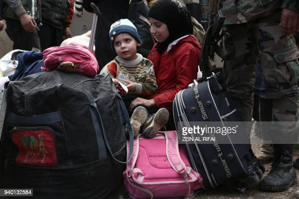 TOPSHOT Syrian children evacuated from Eastern Ghouta sit on luggage after arriving in Qalaat alMadiq some 45 kilometres northwest of the central...