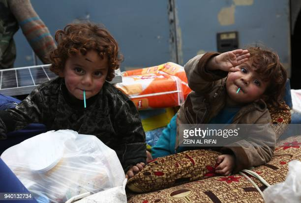 Syrian children evacuated from Eastern Ghouta suck lolly pops after arriving in Qalaat alMadiq some 45 kilometres northwest of the central city of...