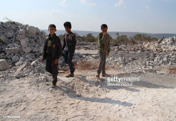 Syrian children gather amidst the rubble of a building at the site of helicopter gunfire which reportedly killed nine people near the northwestern...