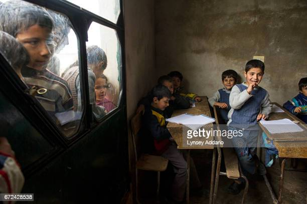 Syrian children go to a small shuttle school set up for families who were scared to send their children far in the midst of war in the village of...