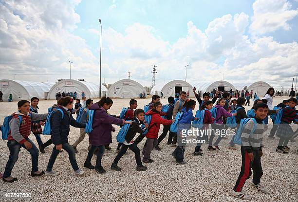 Syrian children go to their lessons at a school in Suruc refugee camp on March 25 2015 in Suruc Turkey The camp is the largest of its kind in Turkey...