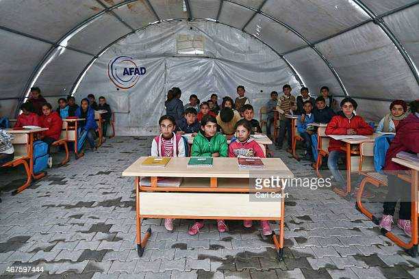 Syrian children listen to a teacher during a lesson in a temporary classroom in Suruc refugee camp on March 25 2015 in Suruc Turkey The camp is the...