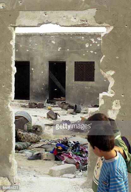 Syrian children look 03 September 2005 at the hideout where five members of the Islamist militant group Jund alSham were killed in clashes with...
