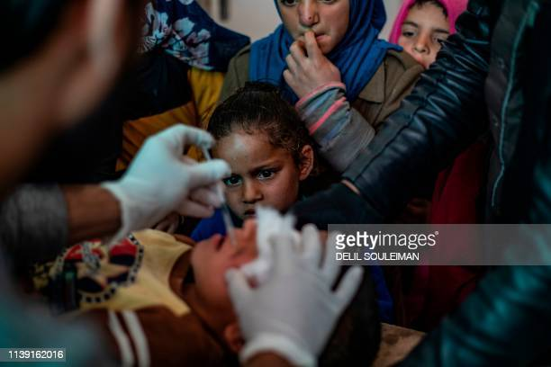 Syrian children look at a doctor injecting a child with a treatment for leishmaniasis skin disease at a health centre in Karama, in northern Syria,...