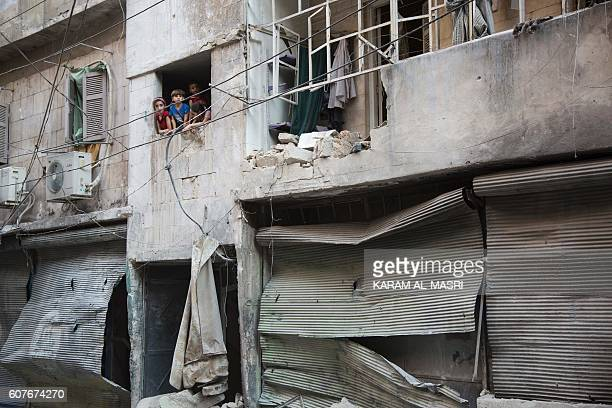 TOPSHOT Syrian children look at the damage following an air strike in Aleppo's rebelcontrolled neighbourhood of Karm alJabal on September 18 2016...