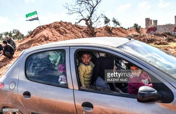 Syrian children look on as people arrive at a check point in the village of Anab ahead of crossing to the Turkishbacked Syrian rebels side on March...