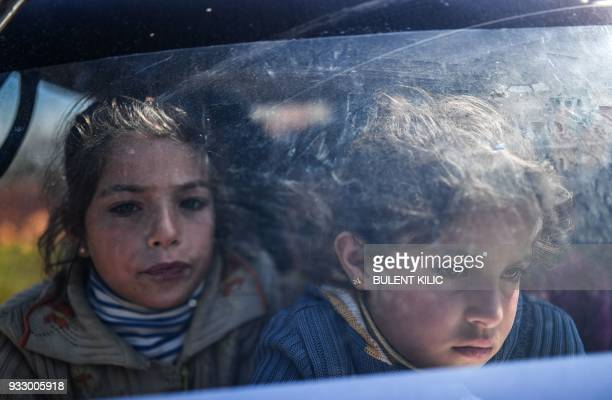 Syrian children look on as they arrive at a check point in the village of Anab ahead of crossing to the Turkishbacked Syrian rebels side on March 17...