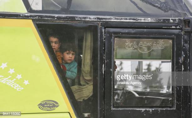Syrian children look outside from the window of a bus as the 17th convoy of vehicles carrying civilians from Syrias Eastern Ghouta district arrive in...