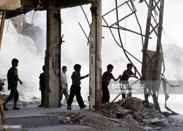 Syrian children play amid the rubble of destroyed buildings being removed by a bulldozer in Harasta on the outskirt of the Syrian capital Damascus on...