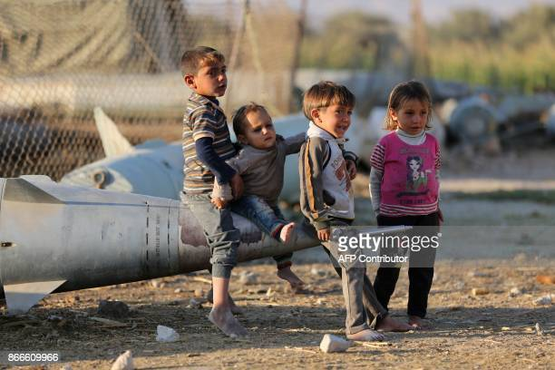 TOPSHOT Syrian children play as they sit on the tip of an abandoned missile at the Ash'ari camp for the displaced in the rebelheld eastern Ghouta...