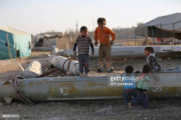 Syrian children play as they sit on the tip of an abandoned missile at the Ash'ari camp for the displaced in the rebelheld eastern Ghouta area...
