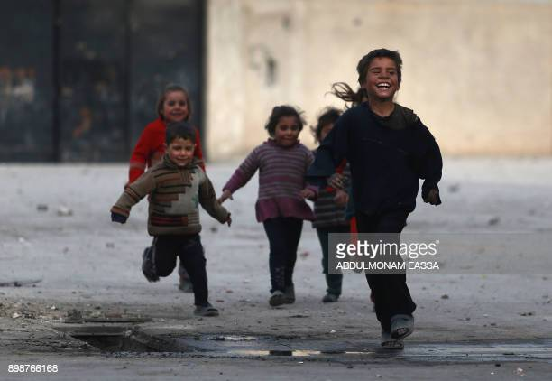 TOPSHOT Syrian children play at a school turned into a shelter for people displaced by the war in the rebelcontrolled town of Hamouria in the eastern...