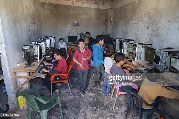 Syrian children play games at a computer center at Atmeh refugee camp housing nearly 60 thousand Syrians left their homes due to the attacks of...