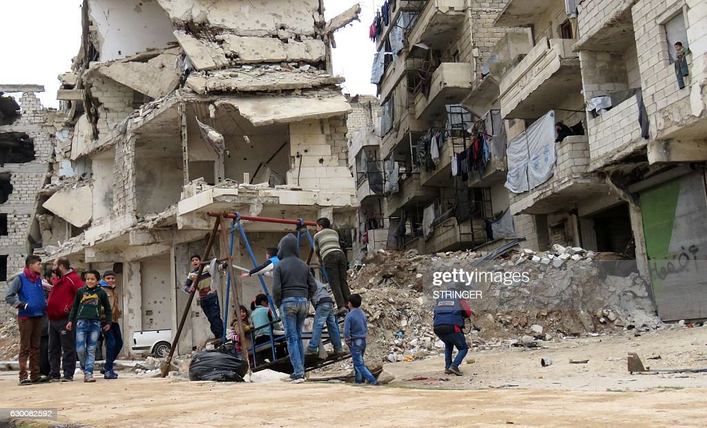 TOPSHOT - Syrian children play in a government-held area of Aleppo on December 16, 2016. Russia announced it was negotiating with the Syrian opposition and seeking a nationwide ceasefire, as the evacuation of civilians and fighters from the last rebel-held parts of Aleppo entered a second day. The Syrian Observatory for Human Rights, a Britain-based monitor of the war, estimated some 8,500 people had left so far, including around 3,000 rebel fighters. Syrian state media reported a figure of around 8,000. / AFP / STRINGER