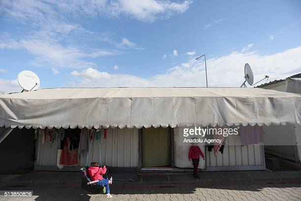 Syrian children play in front of container home at the container city housing 1340 women and more than two thousands children who fled war in their...