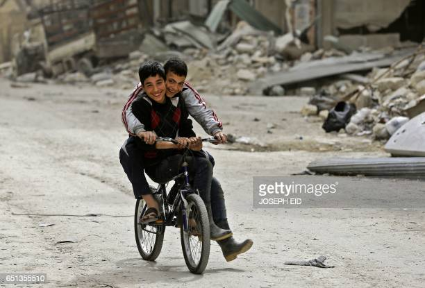 Syrian children play in the once rebelheld Shaar neighbourhood in the northern city of Aleppo on March 10 2017 / AFP PHOTO / JOSEPH EID