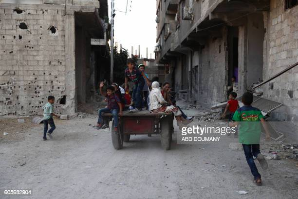 Syrian children play in the street as they celebrate the third day of the AlAdha Eid Muslim holiday in the rebelcontrolled town of Hamouria in the...
