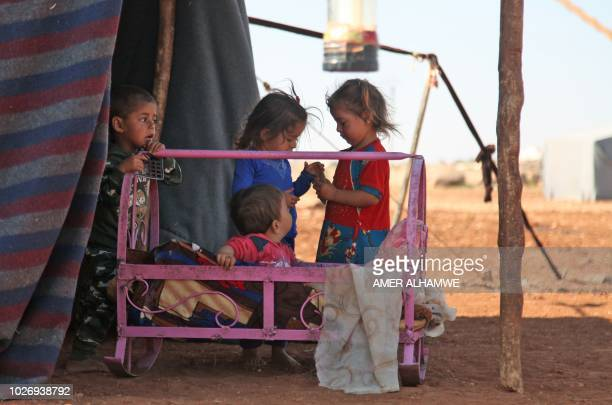 Syrian children play next to a metal crib outside a tent at a camp for displaced civilians fleeing from advancing Syrian government forces close to a...