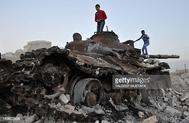 Syrian children play on a destroyed tank in the city of Aleppo on October 7 2012 Syrian rebels lacking heavy arms and air power are braced for the...