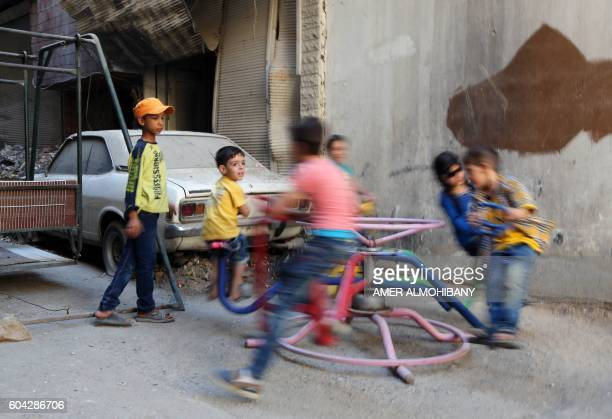 Syrian children play on a ride in the Syrian rebelheld town of Arbin in the eastern Ghouta region on the outskirts of the capital Damascus as they...
