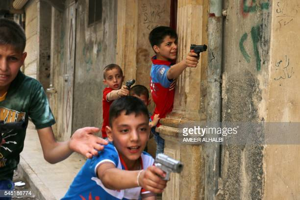 Syrian children play on a street with plastic toy guns in a rebelheld district of the northern city of Aleppo on July 6 2016 during celebrations for...