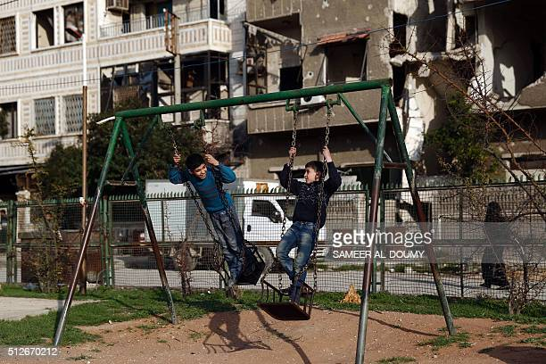Syrian children play on a swing at a park in the rebelheld town of Douma on the eastern edges of the capital Damascus on February 27 on the first day...