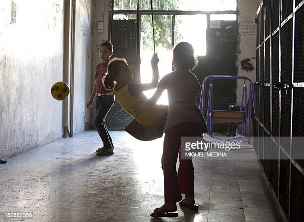 Syrian children play on the ground four of their apartment building in the Aleppo neighbourhood of Izaa on September 26 2012 Children are dying as...