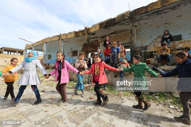 Syrian children play outside their destroyed school in the Frikeh village in Idlib's rebelheld Western countryside on February 18 2018 / AFP PHOTO /...