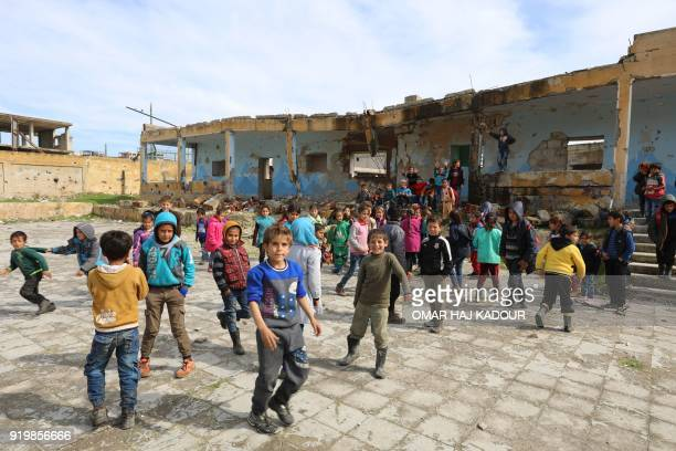 TOPSHOT Syrian children play outside their destroyed school in the Frikeh village in Idlib's Western countryside on February 18 2018 / AFP PHOTO /...