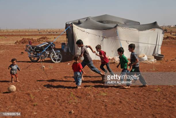 Syrian children play with a ball outside a tent at a camp for displaced civilians fleeing from advancing Syrian government forces close to a Turkish...