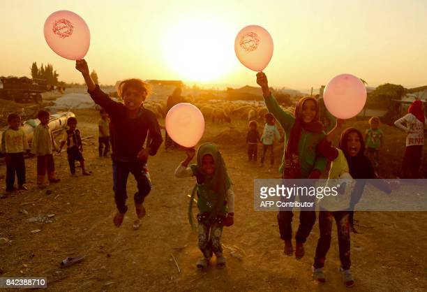 TOPSHOT Syrian children play with balloons in the rebelheld town of Douma on the eastern outskirts of Damascus as Muslims celebrate the third day of...