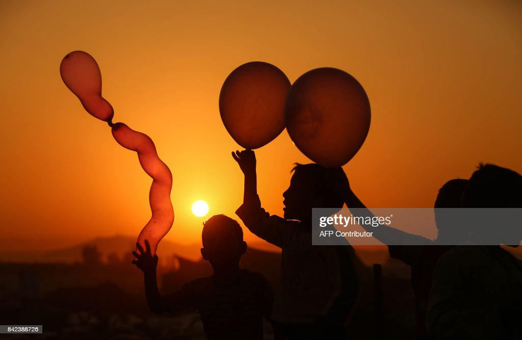 TOPSHOT - Syrian children play with balloons in the rebel-held town of Douma, on the eastern outskirts of Damascus, as Muslims celebrate the third day of the Eid al-Adha holiday on September 3, 2017. /