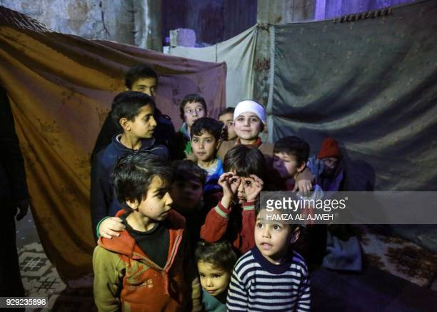 TOPSHOT Syrian children pose for a picture a basement being used as a makeshift bomb shelter in the rebelheld town of Douma in the Eastern Ghouta...