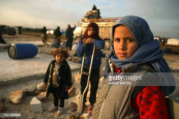 Syrian children pose for a picture as their families prepare to flee a camp for the displaced, east of Sarmada in the north of the northwestern Idlib...