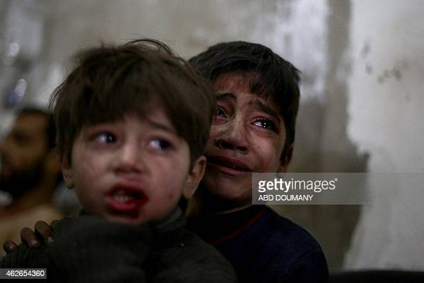 Syrian children react as they wait for treatment at a makeshift hospital in the rebel held area of Douma north east of the capital Damascus following...