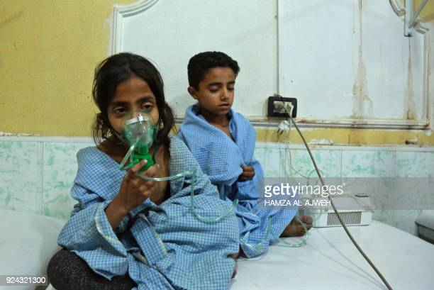 Syrian children receive treatment for a suspected chemical attack at a makeshift clinic on the rebelheld village of alShifuniyah in the Eastern...