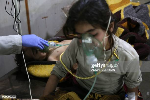 TOPSHOT Syrian children receive treatment for breathing difficulties at a clinic in Syria's Eastern Ghouta on March 7 after regime air strikes Dozens...