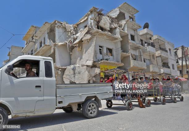 Syrian children ride in the back of a makeshift train towed by a pickup truck past destroyed buildings as they celebrate the first day of the Muslim...