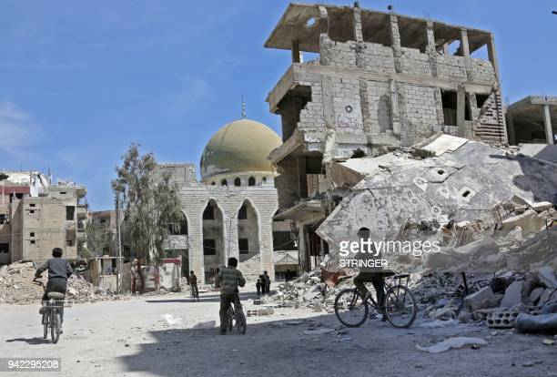 Syrian children ride their bike past destroyed buildings in the former rebel-held town of Zamalka, in Eastern Ghouta on April 5, 2018. / AFP PHOTO /...