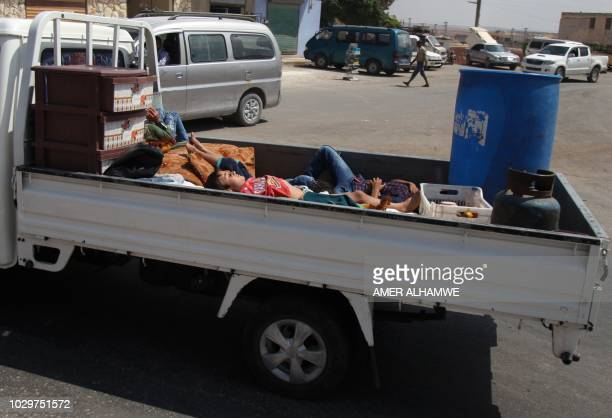 Syrian children ride with their belongings in a truck as they head to safer areas in the town of Khan Sheikhun on the southern edges of the rebelheld...