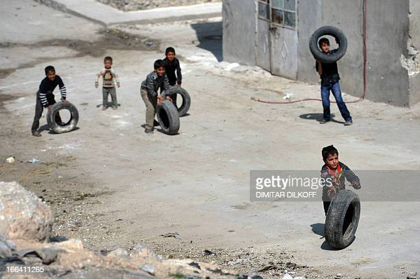 Syrian children roll used car tyres on a street in the northern Syrian city of Aleppo on April 12 2013 A major coalition of Islamist rebels fighting...