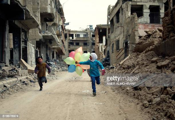 TOPSHOT Syrian children run with balloons past heavily damaged buildings in the neighbourhood of Jobar on the eastern outskirts of the Syrian capital...