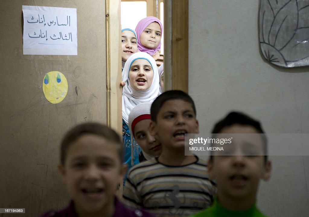 Syrian children sing revolutionary songs at a school in the rebel-controlled area of the northern city of Aleppo on April 22, 2013. The European Union offered fresh aid to Syria's opposition, easing an EU oil embargo in favour of the rebels fighting President Bashar al-Assad, but stopping short of supplying offensive weapons.