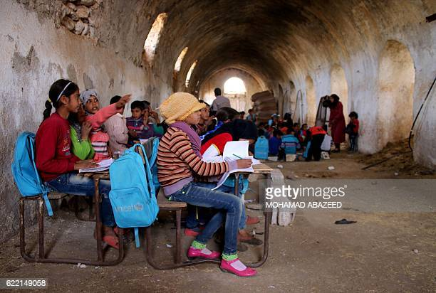 Syrian children sit during class a barn that has been converted into a makeshift school to teach internally displaced children from areas under...