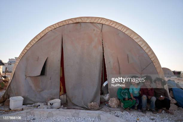 Syrian children sit next to their tent in a camp for the displaced, near the Syrian-Turkish border in the countryside of Idlib on July 31, 2020